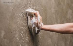 mão usando uma esponja com sabão para limpar parede, manchas